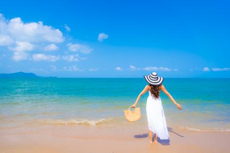 Portrait schöne junge asiatische Frau glückliches Lächeln Freizeit am Strand Meer und Ozean mit blauem Himmel weiße Wolke für Urlaubsreisen