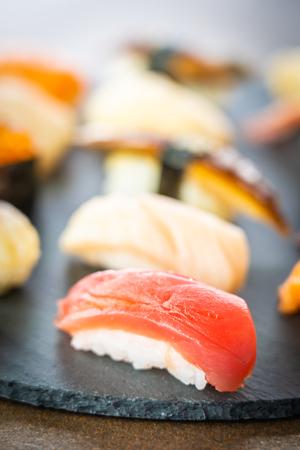 Nigiri sushi set with salmon tuna fish shrimp prawn eel shell and other sashimi on black slate - Japansese food style