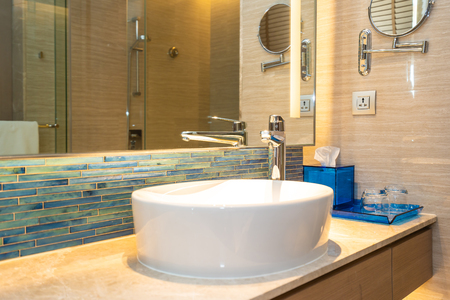 Grifo de agua y decoración de lavabo blanco en el interior del baño de la habitación Foto de archivo