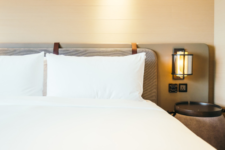 White comfortable pillow on bed decoration in hotel bed room interior Stock Photo
