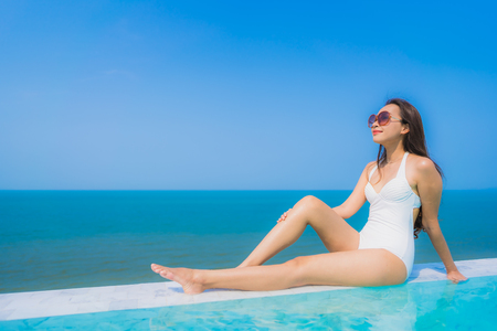 Portrait beautiful young asian woman happy smile relax in swimming pool with sea ocean and blue sky for travel vacation and leisure