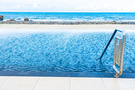 Beautiful outdoor swimming pool in hotel resort with white cloud and blue sky for leisure relax in holiday vacation
