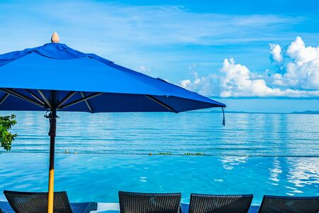 Umbrella and chair around swimming pool nearby sea ocean beach for leisure relax in holiday vacation