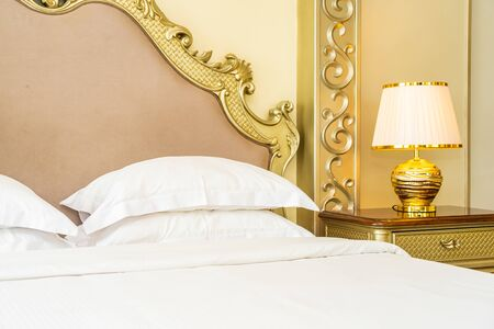 Beautiful luxury comfortable white pillow on bed with light lamp decoration in bedroom interior