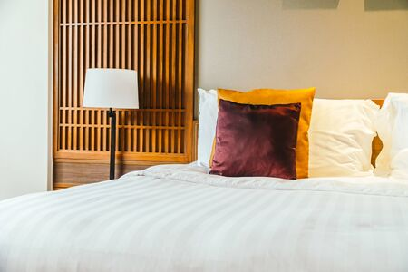 Comfortable pillow on bed with light lamp furniture decoration interior of hotel bedroom
