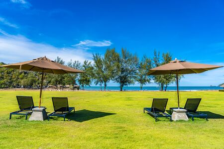 Beautiful outdoor landscape of sea and beach with umbrella and chair around there for leisure travel in holiday vacation
