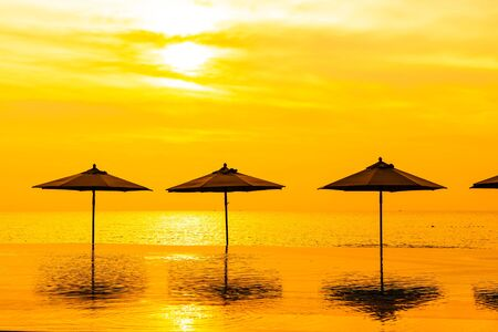 Umbrella and chair around swimming pool neary sea ocean beach at sunrise or sunset time for leisure travel and vacation 스톡 콘텐츠