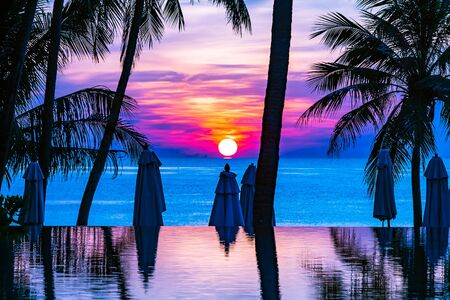 Beautiful outdoor tropical nature landscape of swimming pool with coconut palm tree umbrella and chair nearly sea ocean beach at sunrise time 스톡 콘텐츠