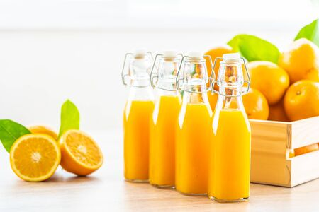 Fresh orange juice for drink in bottle glass on wooden table - Healthy food concept