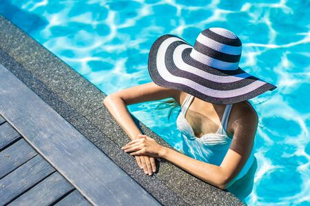 Beautiful young asian woman with hat in swimming pool for travel and vacation concept 스톡 콘텐츠