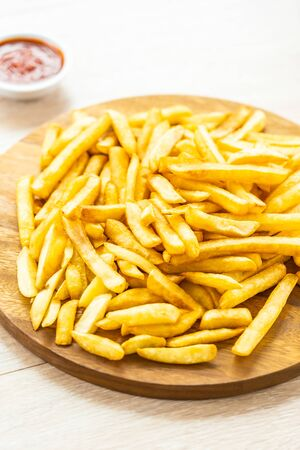 French fries on wooden plate with tomato or ketchup sauce - Junk or Unhealthy food style