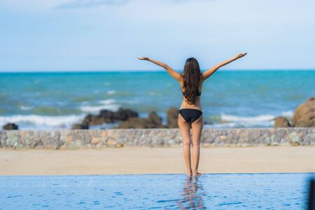 Portrait beautiful young asian woman wear bikini around swimming pool in hotel resort nearly sea ocean beach for leisure relax in holiday vacation time 스톡 콘텐츠