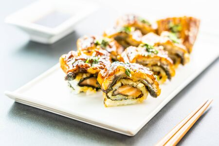 Grilled eel or unagi fish with salmon and vegetable inside sushi maki roll and sweet sauce on white plate - Japanese food style 스톡 콘텐츠