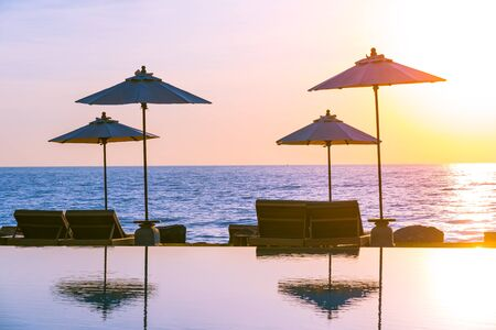 Umbrella and chair around swimming pool for leisure travel and vacation neary sea ocean beach at sunset or sunrise time