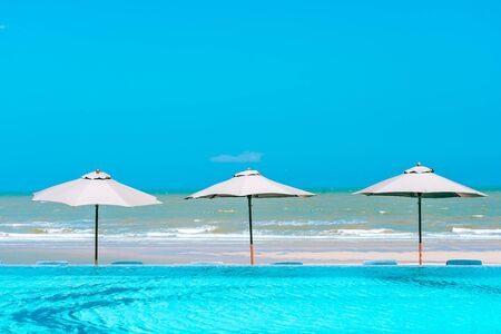 Umbrella and chair around swimming pool neary beautiful landscape of sea ocean beach with blue sky and white cloud for leisure travel and vacation 스톡 콘텐츠