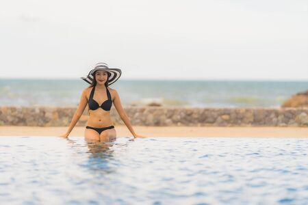 Portrait beautiful young asian woman wear bikini around swimming pool in hotel resort nearly sea ocean beach for leisure relax in holiday vacation time 版權商用圖片