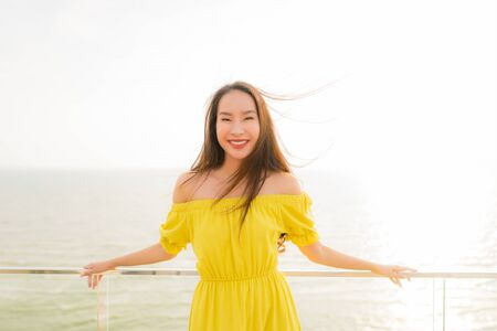 Portrait beautiful young asian woman smile happy and relax at outdoor balcony with sea beach and ocean view for leisure travel and vacation