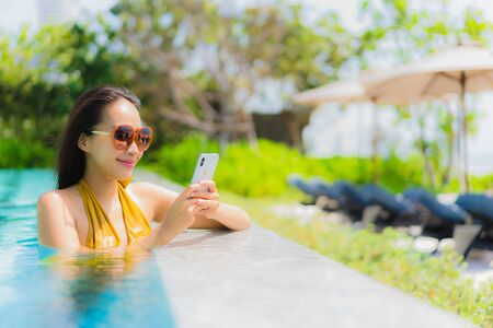 Portrait beautiful young asian woman using mobile phone or cellphone in the swimming pool for holiday vacation travel concept