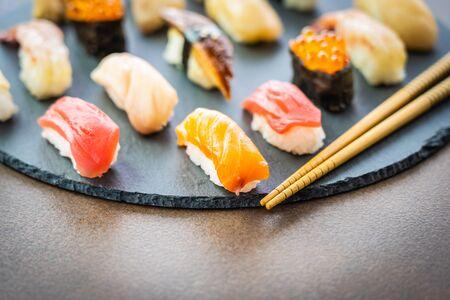 Nigiri sushi set with salmon tuna fish shrimp prawn eel shell and other sashimi on black slate - Japansese food style Imagens