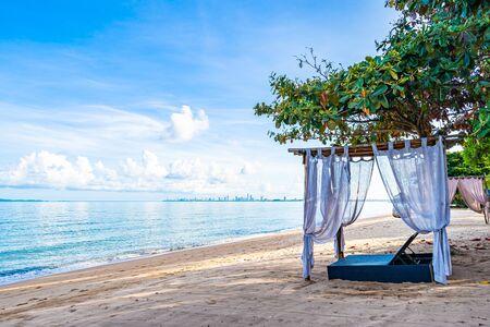 Silla de cama vacía y salón en la playa tropical mar océano con nubes blancas en el cielo azul para viajes de placer y vacaciones de vacaciones Foto de archivo