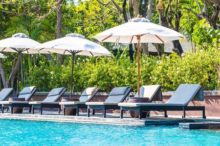 Bellissimo paesaggio dell'oceano mare sul cielo con ombrellone e sedia intorno alla lussuosa piscina all'aperto in hotel resort per viaggi di piacere e vacanze