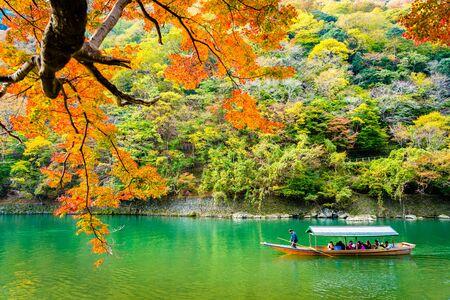 Mooie Arashiyama-rivier met esdoornbladboom en boot rond meer in het herfstseizoen Kyoto Japan