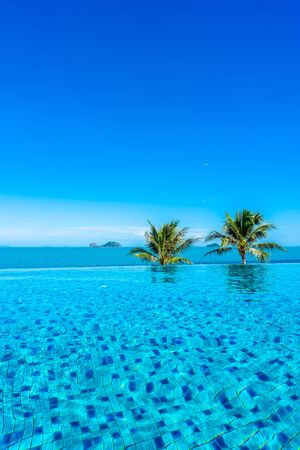 Beautiful luxury outdoor swimming pool with sea ocean around coconut palm tree and white cloud on blue sky for holiday vacation travel