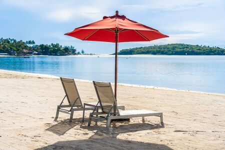 Beautiful outdoor tropical beach sea ocean with umbrella chair and lounge deck around there on white cloud blue sky background for holiday vacation travel 免版税图像