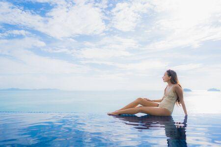 Junge asiatische Frau des Porträts entspannt sich glücklich um den Swimmingpool im Hotel und im Erholungsort für Feiertagsferienreisekonzept