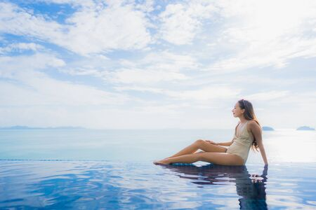 Portrait young asian woman relax smile happy around swimming pool in hotel and resort for holiday vacation travel concept