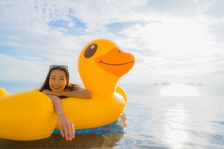 Portrait young asian woman on inflatable float yellow duck around outdoor swimming pool in hotel and resort for holiday vacation concept
