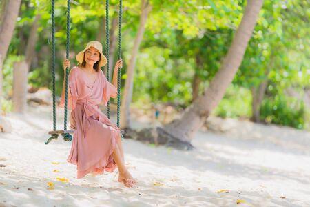 休日の休暇のコンセプトで旅行のためのビーチ海の海のココナッツヤシの木の周りのスイングロープと海に座って肖像画の若いアジアの女性