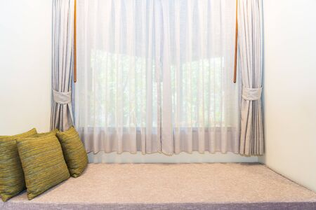 Beautiful comfortable pillow on sofa decoration with curtain interior of room