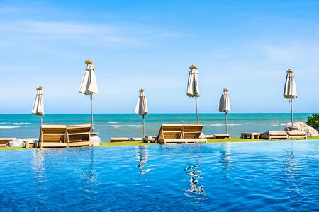 Beautiful outdoor nature landscape with bed deck chair around swimming pool in hotel resort on blue sky