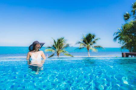 Schöne junge asiatische Frau des Porträts entspannen sich im luxuriösen Außenpool im Hotelresort fast am Strand Meer Ozean für Urlaubskonzept Standard-Bild