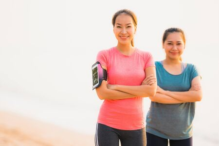 Portrait beautiful young sport asian woman running and exercise on the beach near sea and ocean at sunrise or sunset time for healthy concept 写真素材