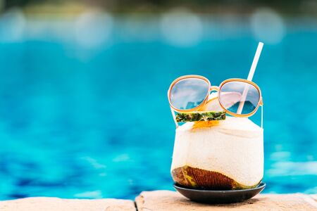 Coconut juice drink around swimming pool in hotel resort for holiday vacation concept