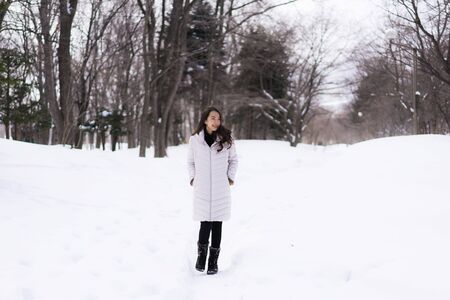 Beautiful young asian woman smiling happy with travel in snow winter season at Hokkaido Japan