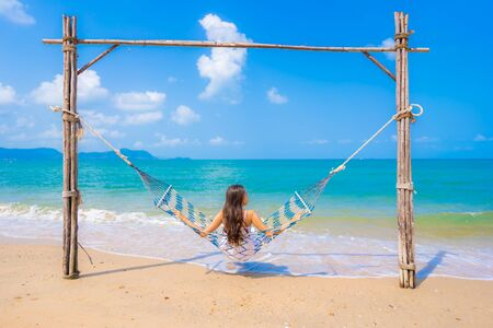 Beautiful young asian woman happy smile leisure on hammock swing around the beach sea and ocean with blue sky white cloud for vacation travel