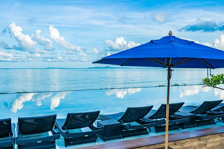 Umbrella and chair around swimming pool in hotel resort near sea ocean beach for leisure relax in holiday vacation