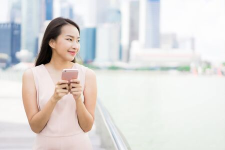 Beautiful asian woman using smartphone or mobile phone for talking or text