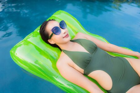 Portrait beautiful young asian woman smile happy relax and leisure on the rubber floating inflatable around the swimming pool hotel resort for travel and vacation concept
