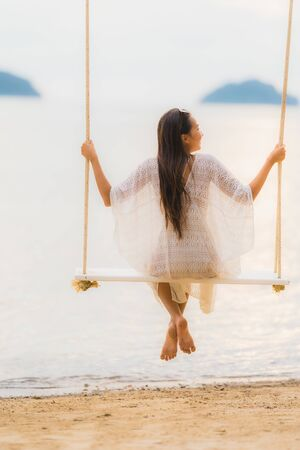 Portrait beautiful young asian woman sitting on the swing around beach sea ocean for relax in holiday vacation concept Stock Photo