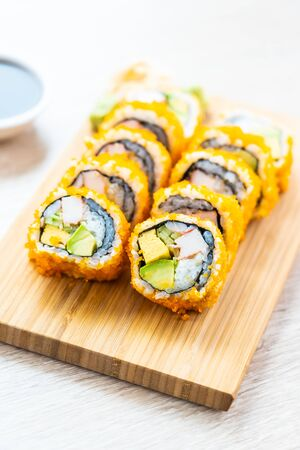 California maki rolls sushi on wooden plate with sauce and chopsticks, Japanese food style