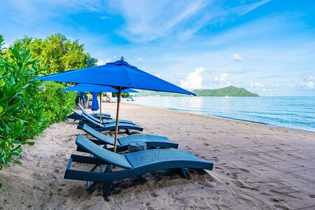 Beautiful umbrella and empty bed chair on the tropical beach and sea with white cloud blue sky background for leisure travel in holiday vacation