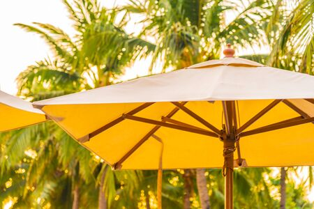 Umbrella and deck chair on the beautiful beach and sea at sunrise time for travel and vacation
