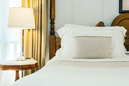 Almohada blanca y manta en la decoración de la cama en el hermoso interior del dormitorio de lujo Foto de archivo