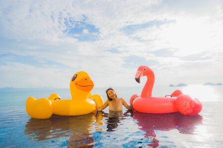 Portrait young asian woman on inflatable float yellow duck and pink flamingo around outdoor swimming pool in hotel and resort for holiday vacation concept