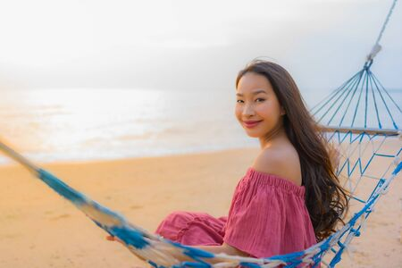 Portrait beautiful young asian woman sitting on the hammock with smile happy nearly beach sea and ocean for leisure travel and vacation at sunset time Stock Photo