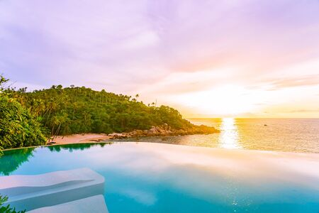 Beautiful outdoor infinity swimming pool with sea ocean view and white cloud blue sky at sunrise time for holiday vacation and travel